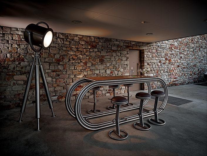 Theke Ligna und Decos Barhocker in einem Gewölbe mit Spotlampe