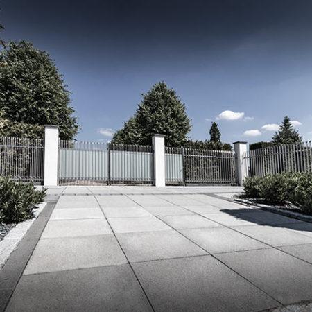 Einfahrt für Autos mit abgrenzendem Ceria2-Zaun und Torelement aus Edelstahl