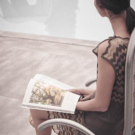 Outdoor Designstuhl Ames mit lesender Frau im Garten