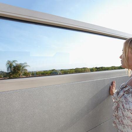 Frau vor Schallschutzwand mit Sichtfenster aus Glas