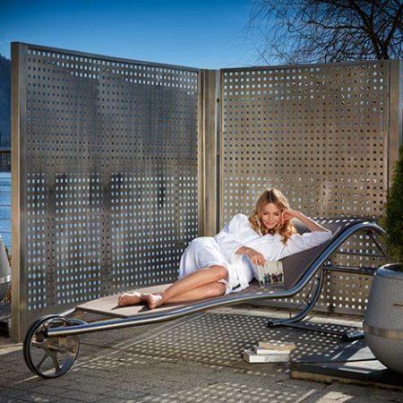 Frau auf Lignum-Liege mit Sichtschutzwand Seapes aus Edelstahl